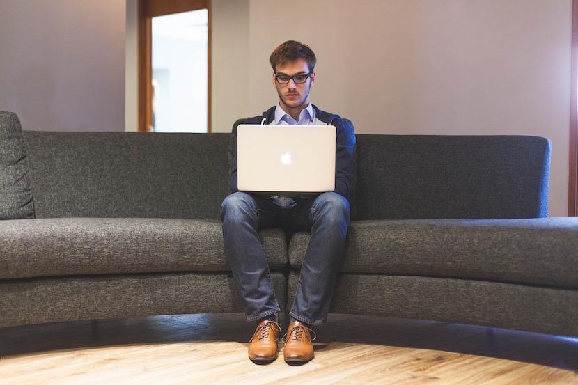ソファーでMacをいじる男性